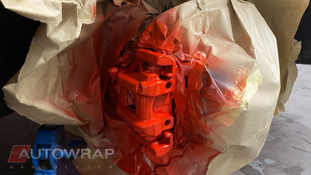 A Calliper taped off to protect the rest of the metal. The Calliper and the protective paper are covered in fresh red paint.