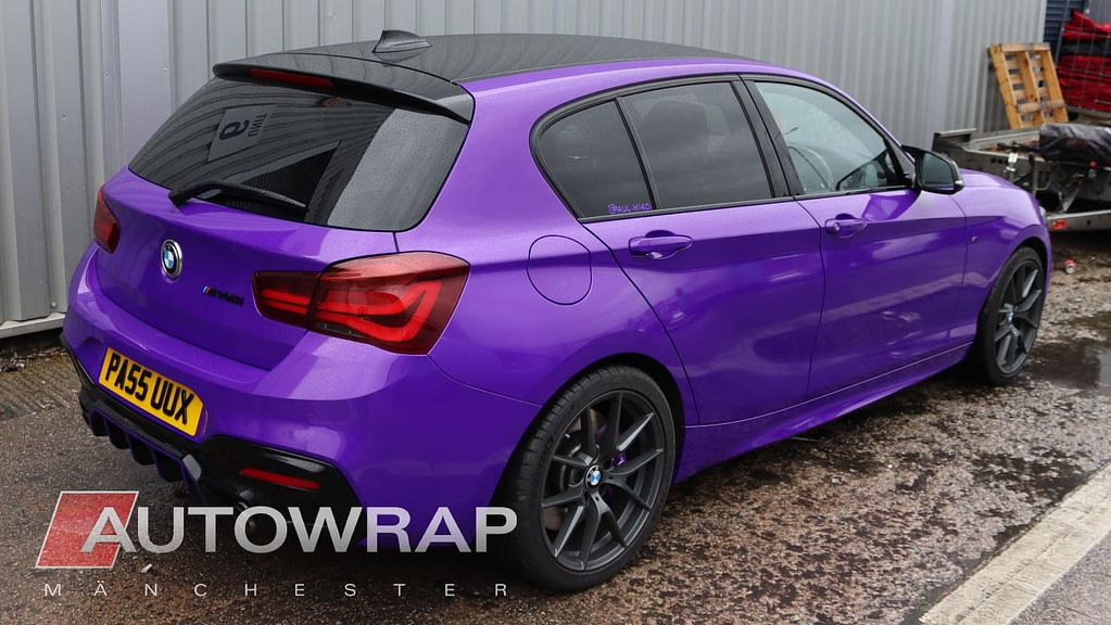 A BMW M140i wrapped in a glossy, bright purple vinyl