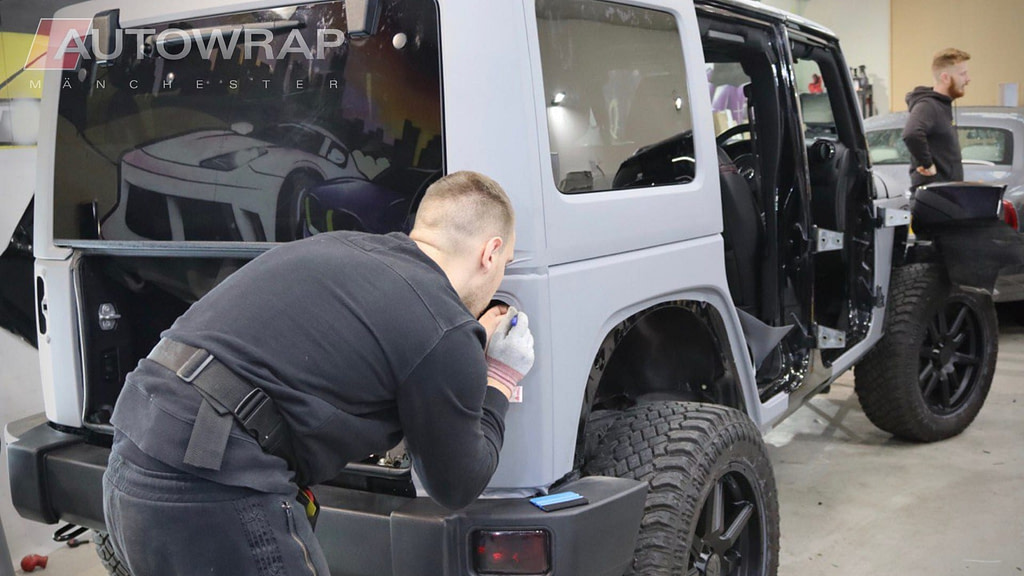 A light grey vinyl wrap being applied to a car