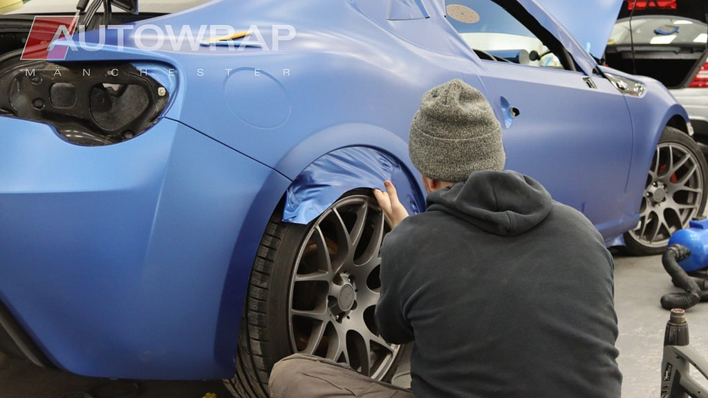 Dark blue vinyl wrap being applied to the side of a car in our workshop