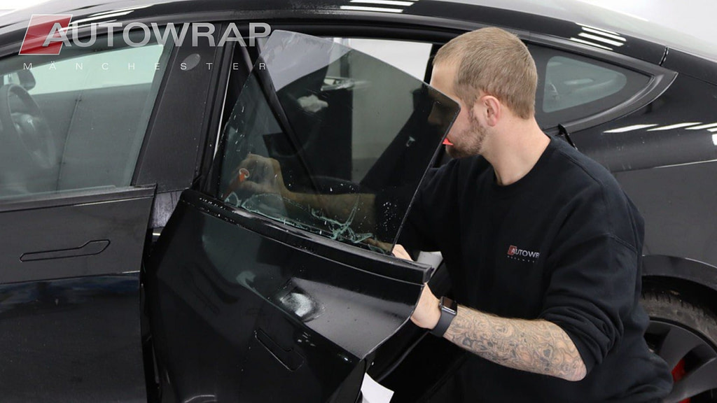 Window tint being applied to the side window of a car in the Auto Wrap Manchester workshop