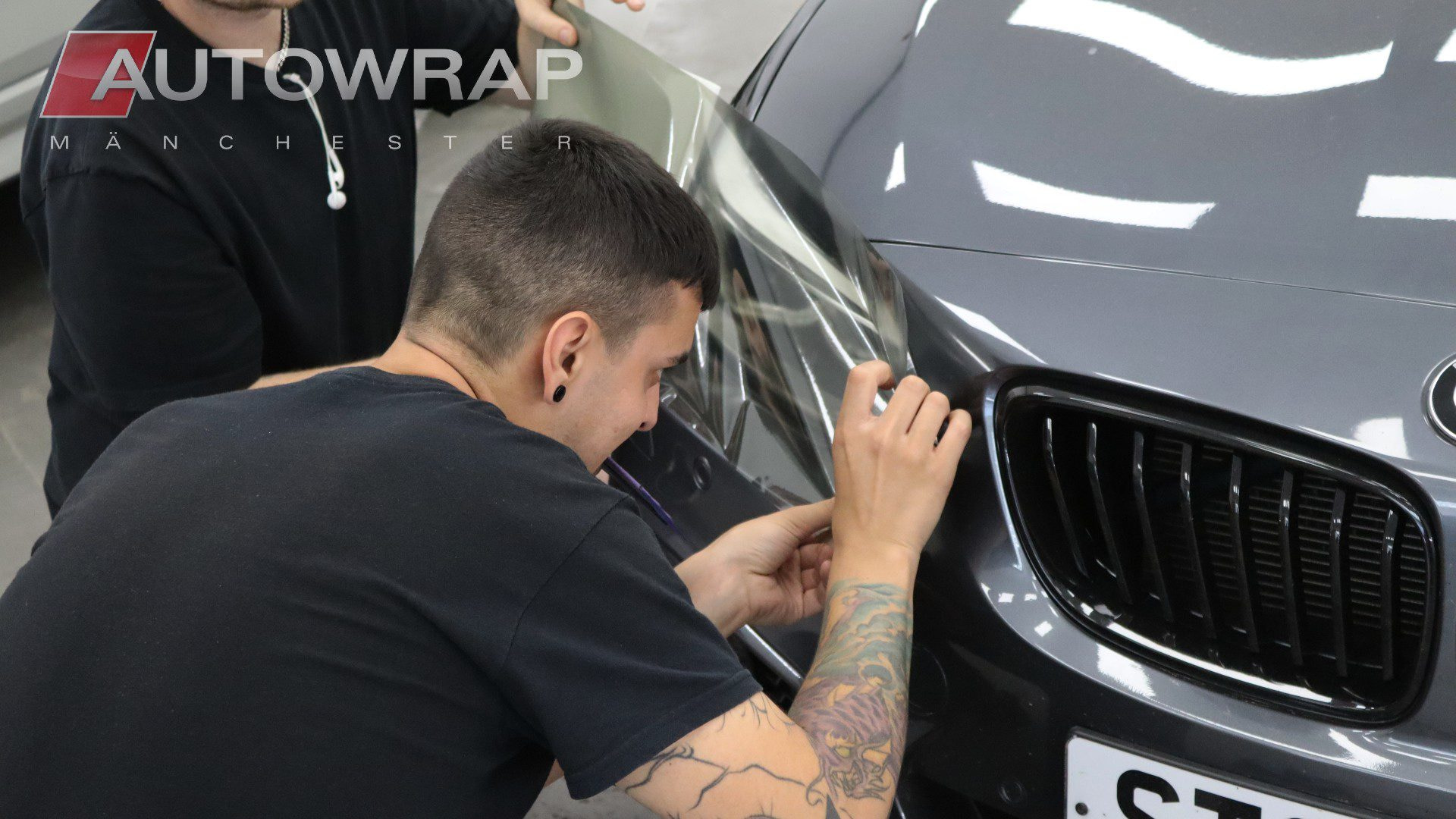 a wrapper applying film to the front headlights of a grey car.