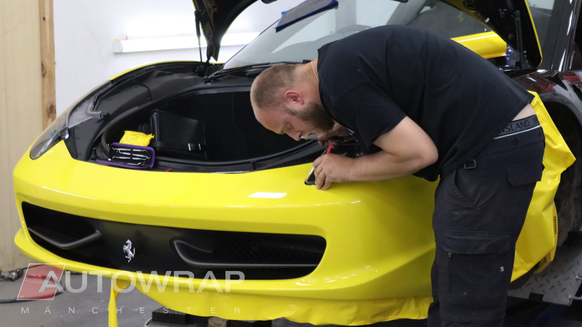 a wrapper working on a yellow car