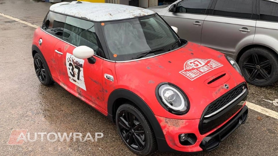 A mini cooper with a custom printed wrap designed to look like a retro rally car