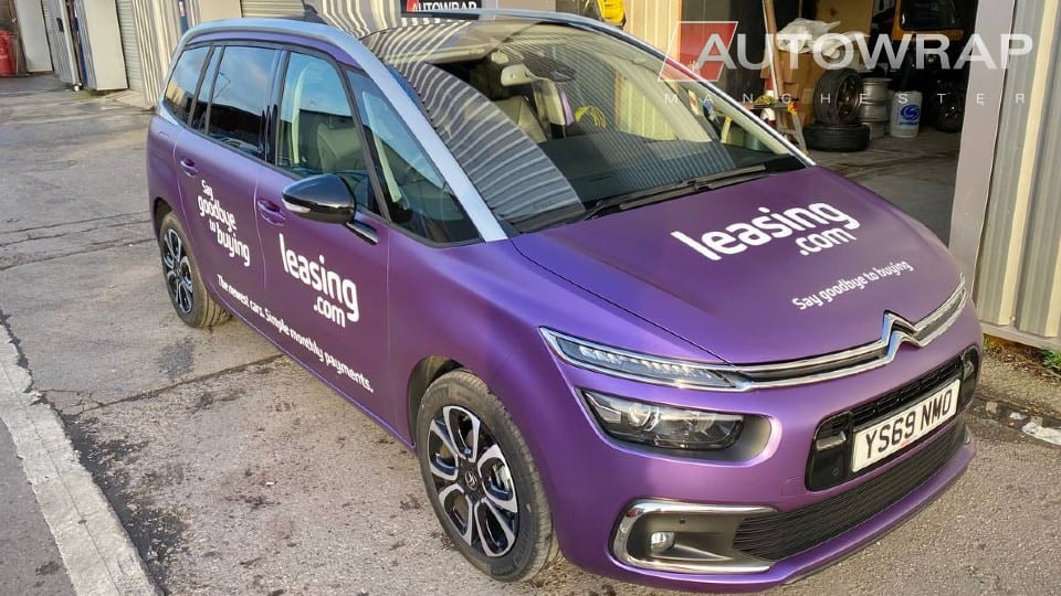 """A purple wrapped car with applied graphics for """"leasing.com"""" on the rear and sides."""